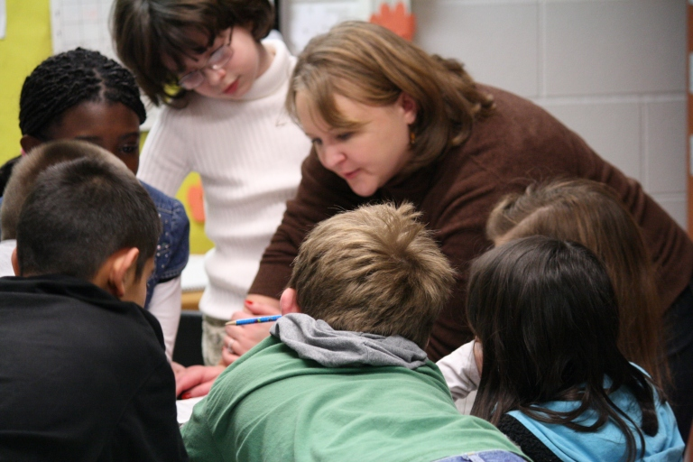 Students gather around Julie during collaborative writing exercise