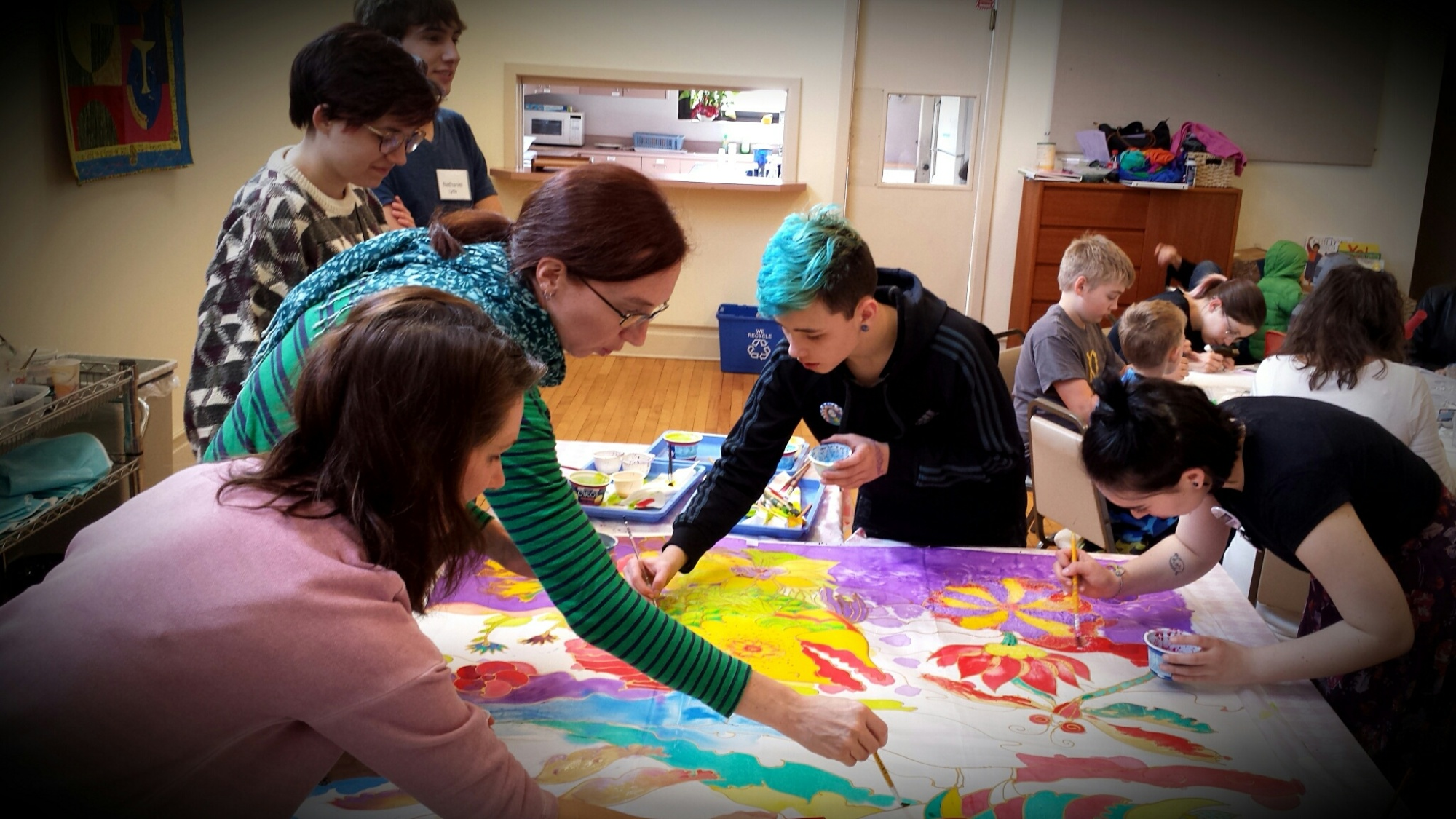 Students and adults paint bright colors on fabric during Sofiya's workshop